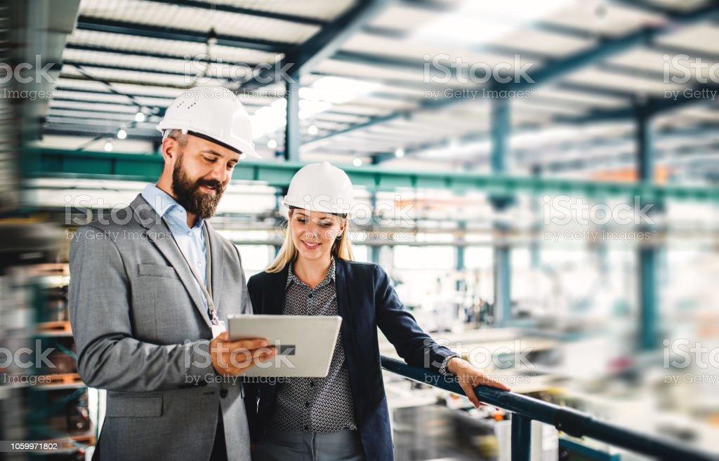 Ein Porträt von industriellen Mann und Frau Ingenieur mit Tablet-PC in einer Fabrik arbeiten. – Foto
