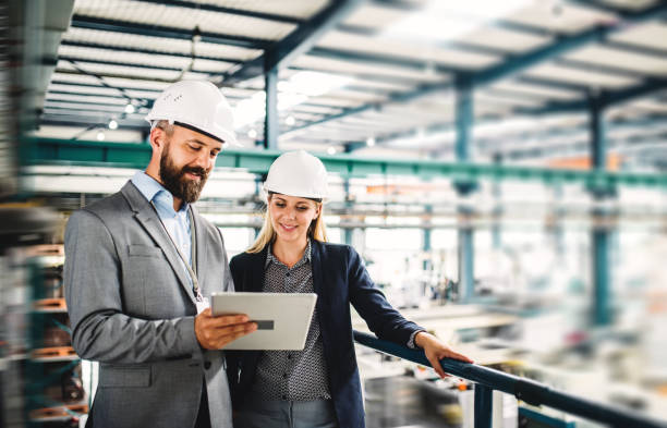 A portrait of an industrial man and woman engineer with tablet in a factory, working. A portrait of a mature industrial man and woman engineer with tablet in a factory, working. engineer stock pictures, royalty-free photos & images