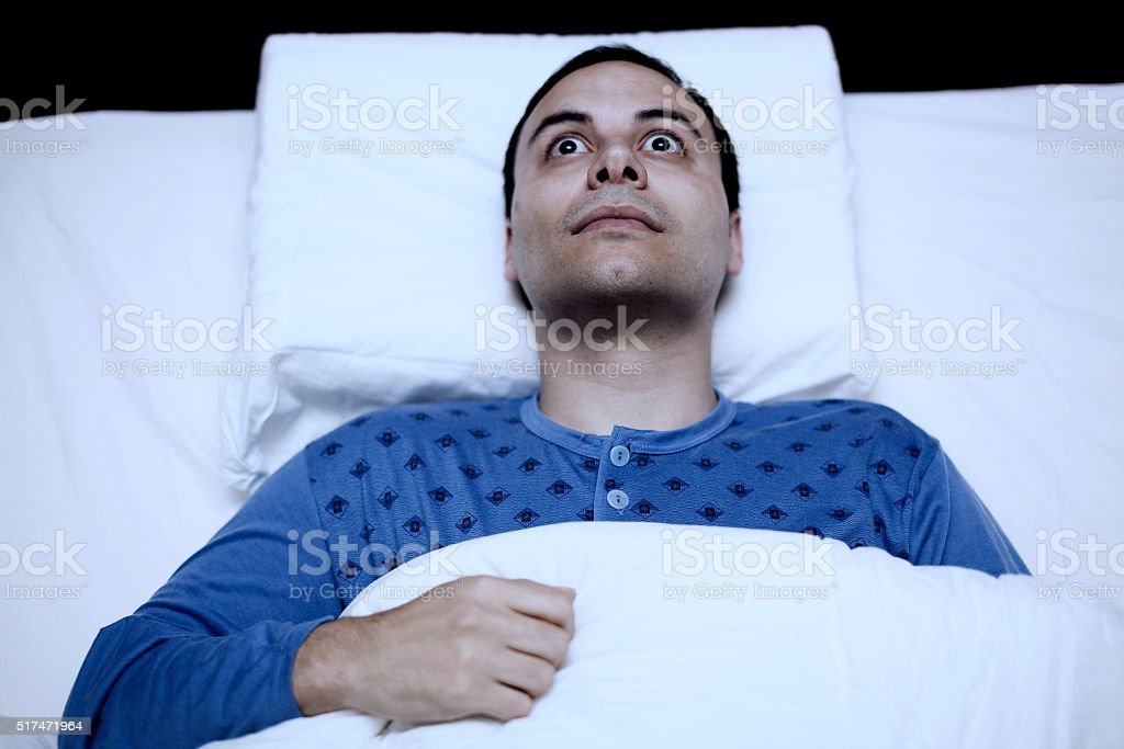 Portrait of an insomniac man trying to sleep stock photo