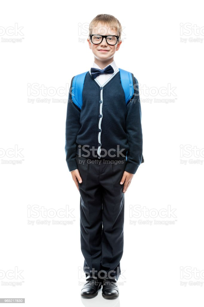 portrait of an intelligent schoolboy in school uniform, glasses and with a backpack in full length on a white background zbiór zdjęć royalty-free