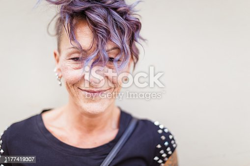 518704237istockphoto Portrait of an modern Italian woman, leaning on the yellow wall 1177419307