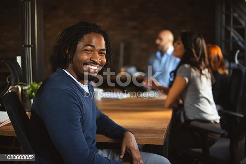 Portrait of an African American office worker. He is smiling and looking at camera and the rest of his team is talking in the background.