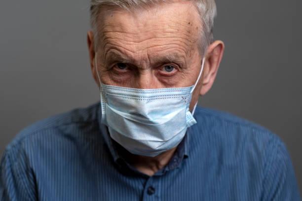 porträt eines alten mannes in einer medizinischen schutzmaske. - einzelner senior stock-fotos und bilder