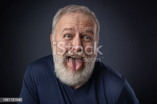 661896674istockphoto Portrait of an old man with the tongue out 1051731340