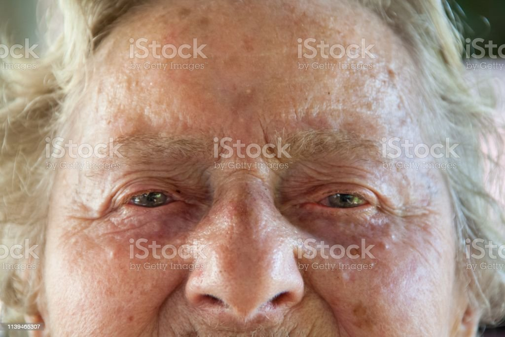 Close-up of a white senior woman, sad face and details of the aging...