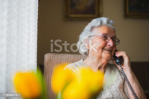 Old lady speaks to her daughter and son by telephone, and she is rejoicing because they are coming to visit her soon.