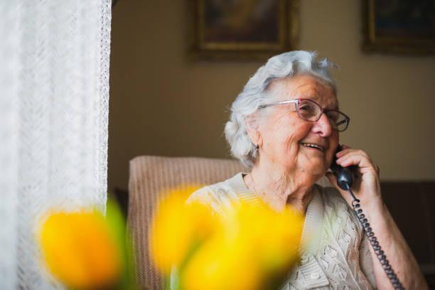 verticale d'une femme plus âgée parlant avec le téléphone - seulement des femmes seniors photos et images de collection