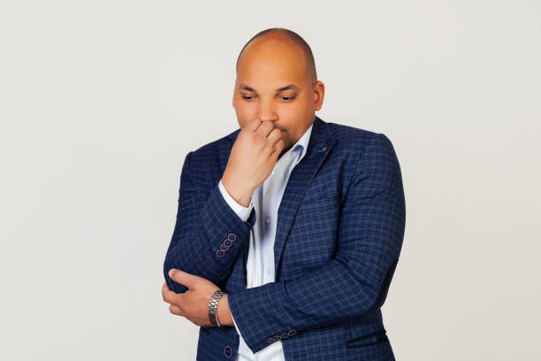 Portrait of an upset young African American businessman guy, looks tense and nervous with hands on lips, biting his nails. Anxiety problem. Standing on a gray background. stock photo