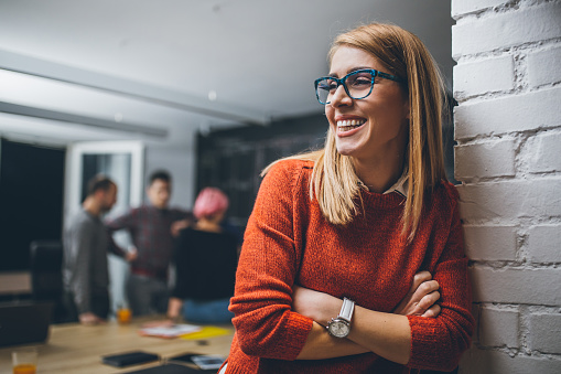 Portrait of an young female  team leader, entrepreneur, standing in the office, smiling