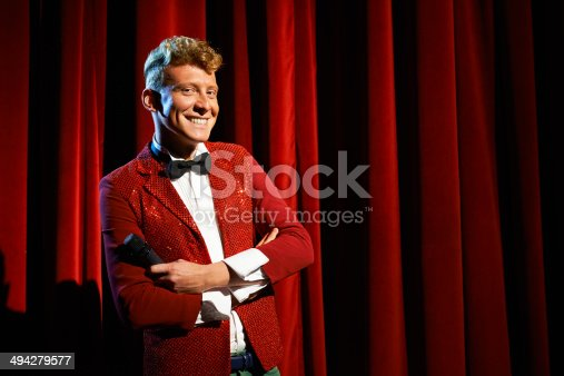 istock Portrait of anchorman at show against red curtain 494279577