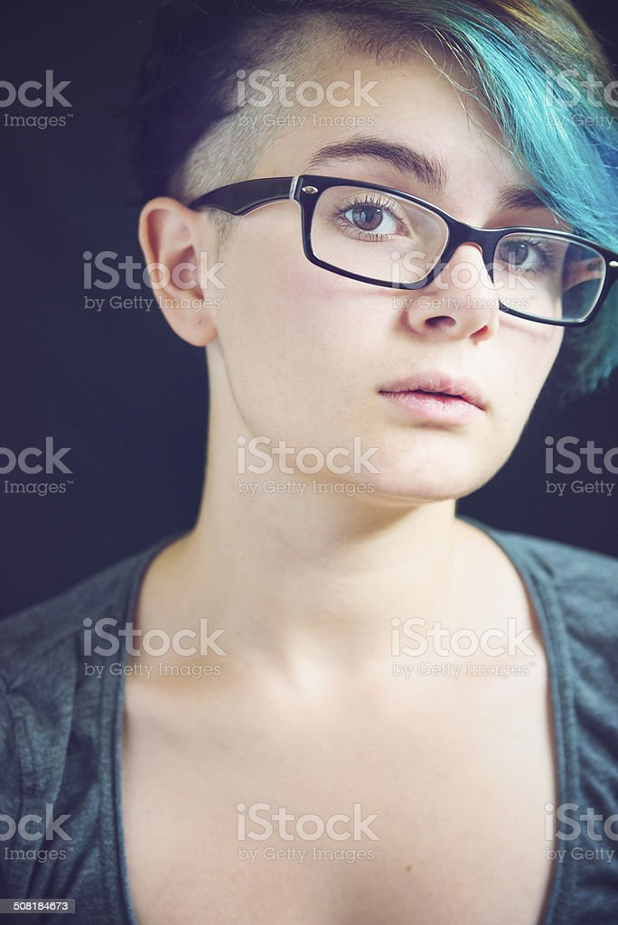 Portrait of androgynous young woman with blue hair and glasses. stock photo
