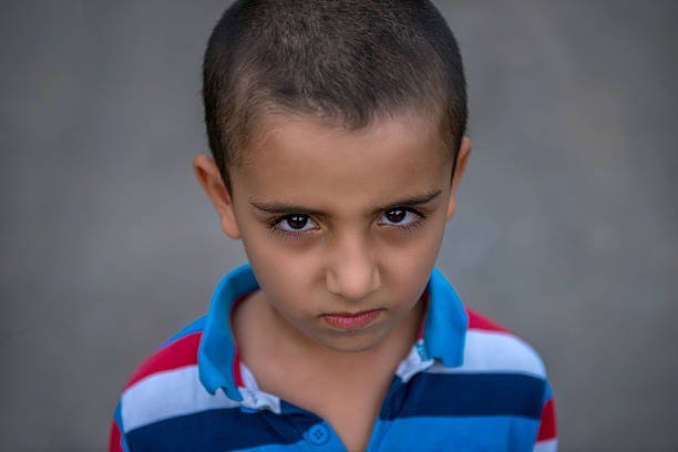 Portrait of angery boy looking at camera stock photo