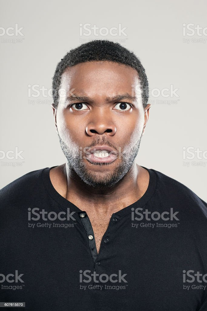 Portrait of angry afro american young man Portrait of angry afro american young man wearing black t-shirt, standing against grey background, clenching teeth, staring at camera. Adult Stock Photo