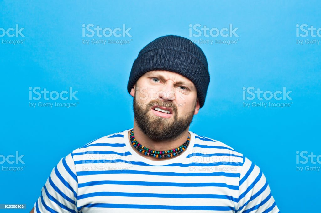 Portrait of angry bearded sailor against ble background Portrait of angrybearded man wearing striped t-shirt and beanie hat looking at camera. Studio shot, blue background. 30-34 Years Stock Photo