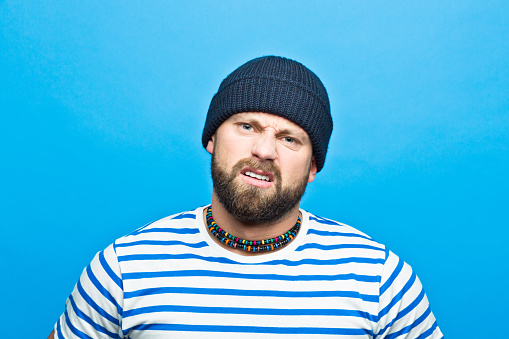 Portrait Of Angry Bearded Sailor Against Ble Background Stock Photo - Download Image Now