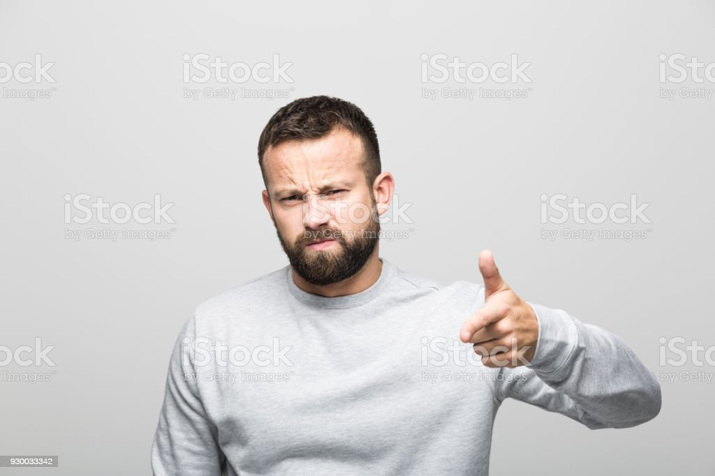 Portrait of angry bearded young man pointing at camera Portrait of angry bearded young man pointing at camera with index finger. Studio shot, grey background. 30-34 Years Stock Photo
