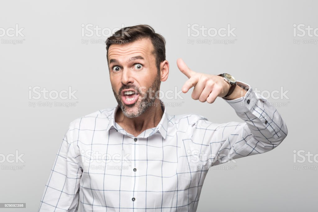 Portrait of angry businessman pointing at camera, grey background Studio portrait of bossy businessman wearing white shirt, pointing at camera against grey background. 30-39 Years Stock Photo