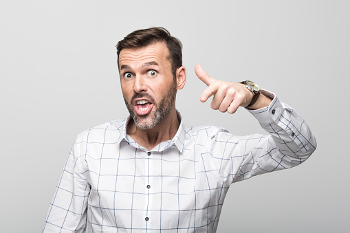 Portrait Of Angry Businessman Pointing At Camera Grey Background Stock Photo - Download Image Now