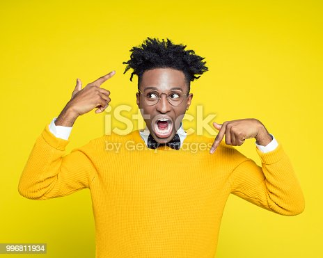 istock Portrait of angry nerdy young man gesturing against yellow background 996811934