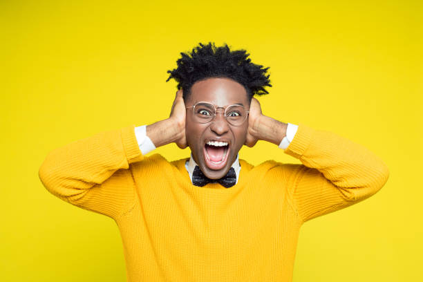 Portrait of angry nerdy young man shouting against yellow background Portrait of angry nerdy young afro american man wearing yellow sweater and black bow tie shouting at the camera against yellow background. hands covering ears stock pictures, royalty-free photos & images