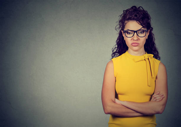 Portrait of angry woman in yellow dress standing with arms folded on gray background stock photo