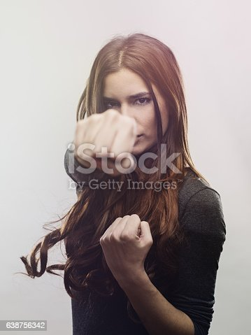 istock Portrait of angry woman punching the air 638756342