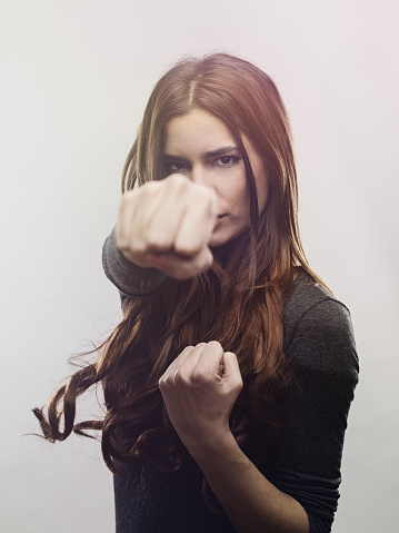 Portrait of angry woman punching the air. Close-up of aggressive young female. She is against white background. Vertical studio photography from a DSLR camera. Sharp focus on eyes.