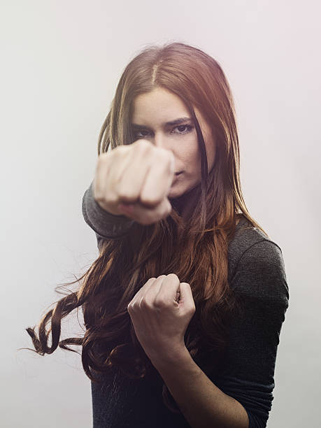 portrait of angry woman punching the air - punching stock photos and pictures