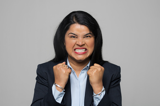 Portrait of angry young businesswoman clenching teeth and showing fists while standing against grey background.