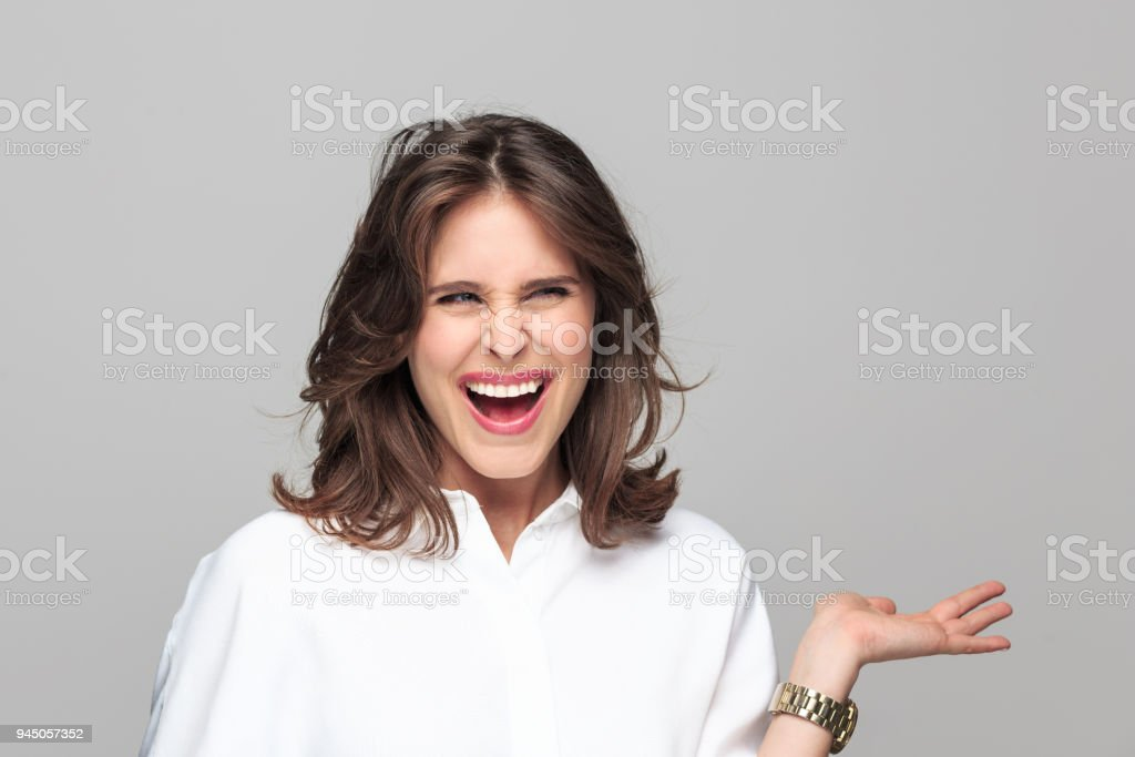 Portrait of angry young businesswoman Portrait of angry young businesswoman screaming at camera against grey background. 25-29 Years Stock Photo