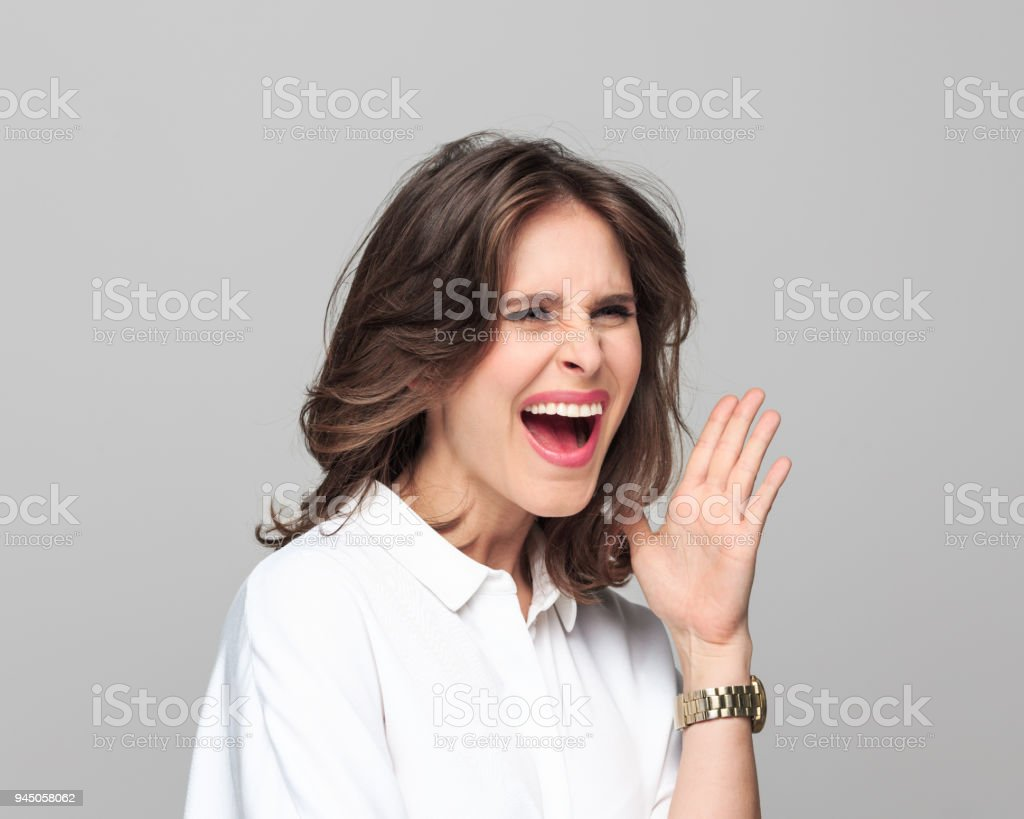 Portrait of angry young businesswoman Portrait of angry young businesswoman screaming against grey background. 25-29 Years Stock Photo