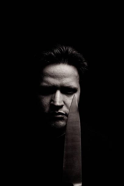 Retrato de jovem homem irritado com faca, Low Key - foto de acervo