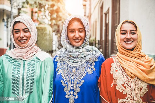 Portrait of arabian girls outdoor in city street - Young islamic women smiling on camera - Youth, friendship, religion and culture concept - Focus on faces