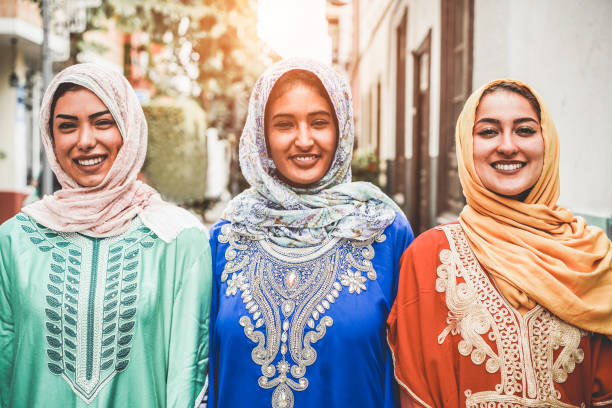 portrait of arabian girls outdoor in city street - young islamic women smiling on camera - youth, friendship, religion and culture concept - focus on faces - pakistano foto e immagini stock