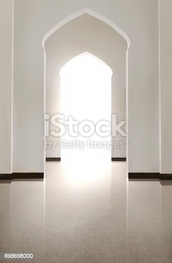 istock Portrait of arch door with tiled floor and white wal 698698000