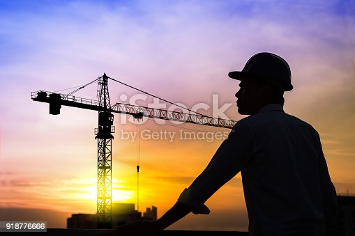 istock portrait of architect silhouette wear a helmet at construction site with crane background and sunset 918776666
