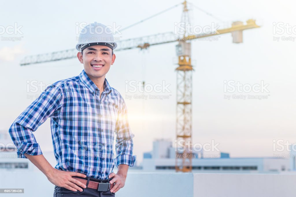 Portrait of architect wear a white helmet with construction site and crane background. He has smile because his project were success. stock photo