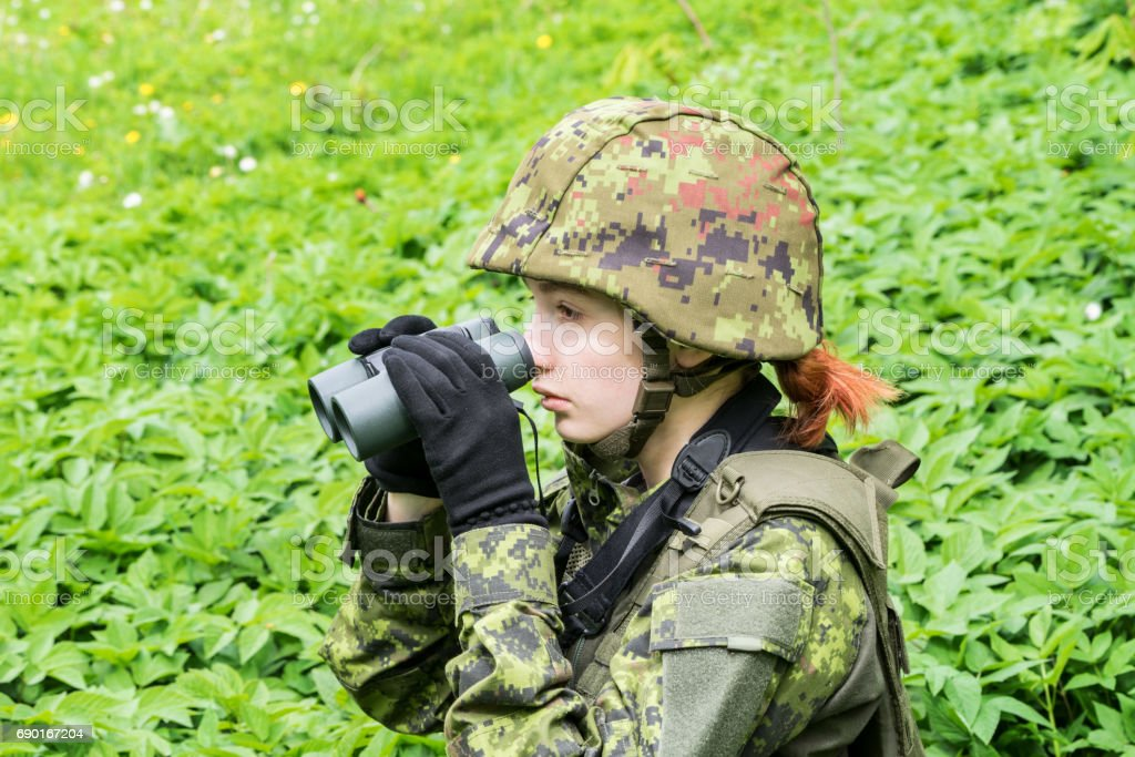 Portrait of armed woman with camouflage. Young female soldier observe with binoculars. Child soldier with gun in war, green goutweed background.  Military, army people concept stock photo