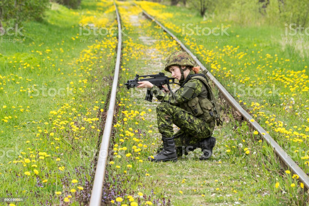 Portrait of armed woman with camouflage. Young female soldier observe with firearm on rail. stock photo