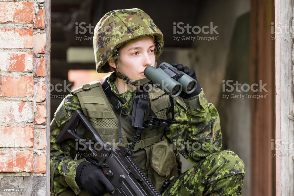 Portrait of armed woman with camouflage. Young female soldier observe with binoculars. Child soldier with gun in war, house ruins background.  Military, army people concept stock photo