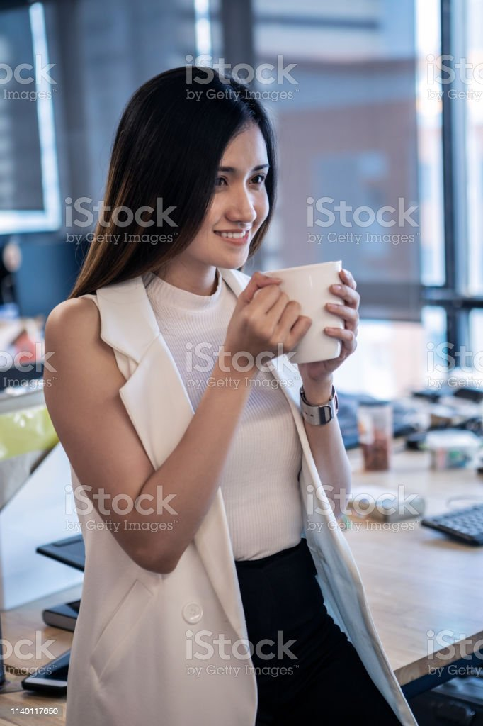 Standing By Her Desk Holding Her Coffee Cup