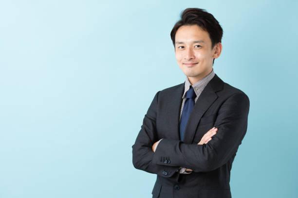 青の背景に分離したアジア系のビジネスマンの肖像画 - 男性のみ ストックフォトと画像