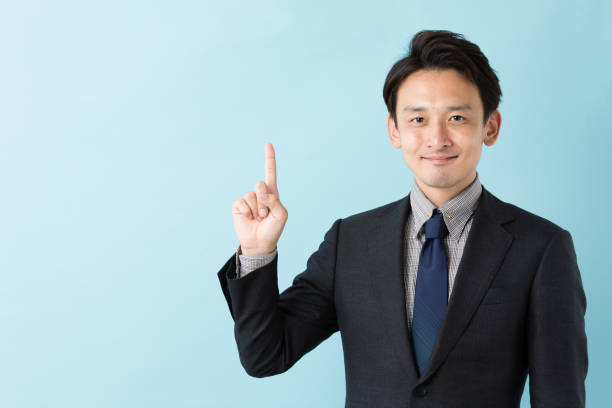 portrait of asian businessman isolated on blue background portrait of asian businessman isolated on blue background index finger stock pictures, royalty-free photos & images