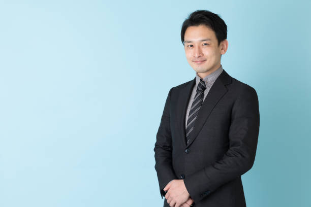 青の背景に分離したアジア系のビジネスマンの肖像画 - ビジネスポートレート ストックフォトと画像