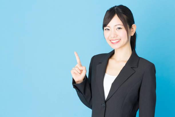 青の背景に分離されたアジアの実業家の肖像画 - 指差す ストックフォトと画像