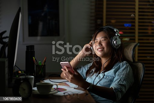 842214626istockphoto Portrait of Asian Businesswoman listening the music via headphone and smart mobile phone with relax action on the table in workplace at late time, Work hard and too late concept 1067853420