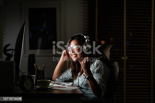 istock Portrait of Asian Businesswoman listening the music via headphone and smart mobile phone with glad action on the table in workplace at late time, Work hard and too late concept 1071574428