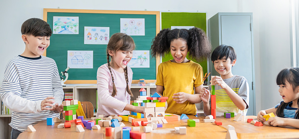 Portrait of asian caucasian little children playing colorful blocks in classroom. Learning by playing education group study concept. International pupils doing activities brain training in primary school.