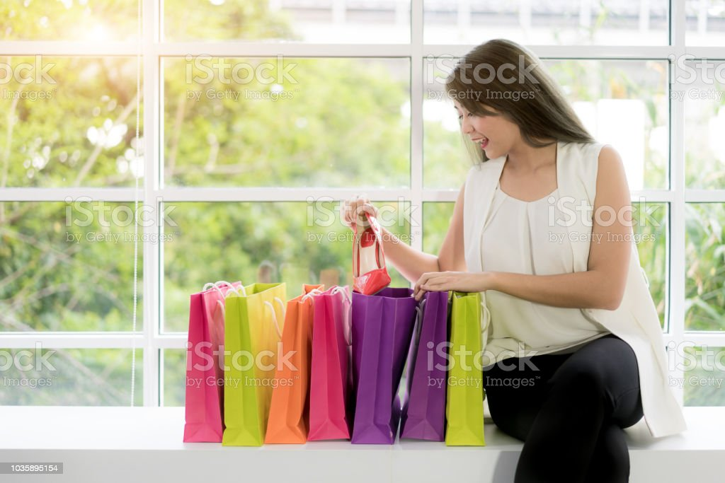 Portrait of Asian cheerful woman holding shopping bags and looking at...