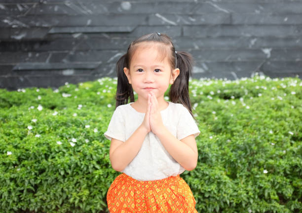 portrait of asian child girl in traditional thai dress praying. - philippines girl stock photos and pictures